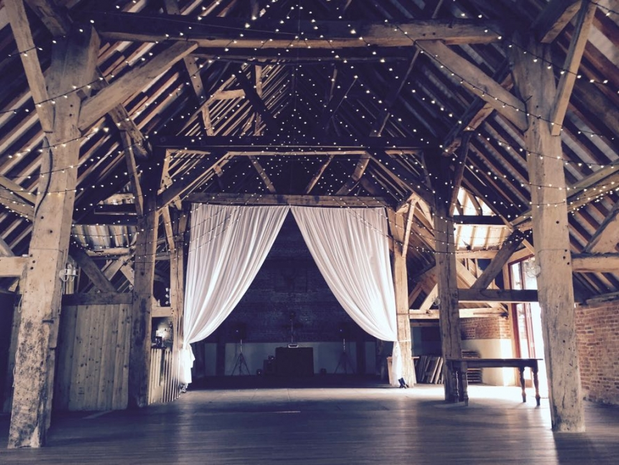 A lovely rustic barn with a makeover of white curtains and fairy-light canopu