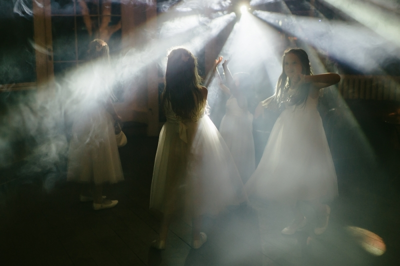 Five bridesmaids dancing in white light.