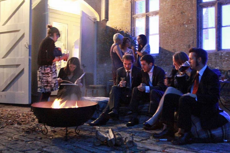 Image of people sitting around a fire-pit at night.