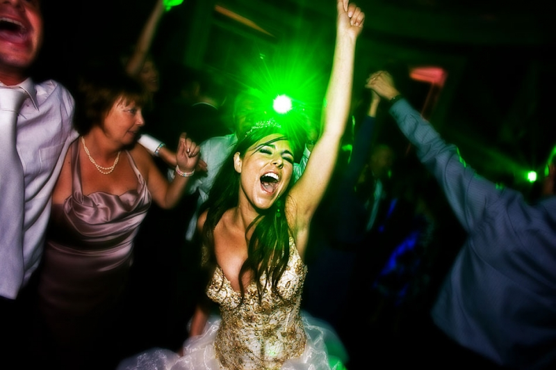 An image of a bride with her hands in the air and eyes closed.
