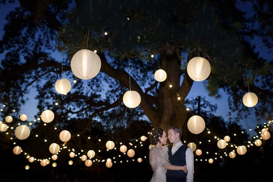 Image of a smartly dressed bride and groom embracing underneath a large tree with festoon lighting.
