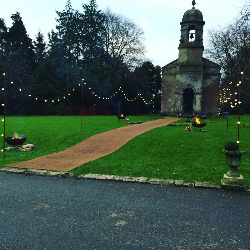 Image of a church with festoon lighting runniong down the entrance and fire-pits on the lawn.