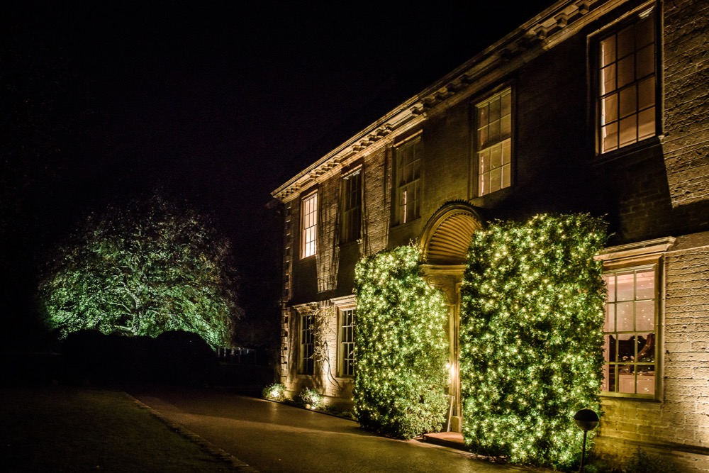 Image of the exterior of Babington House Hotel with additional lighting in bushes.