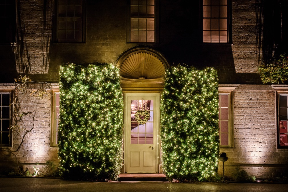 Front of Babington House with bush lighting either side of the front door.