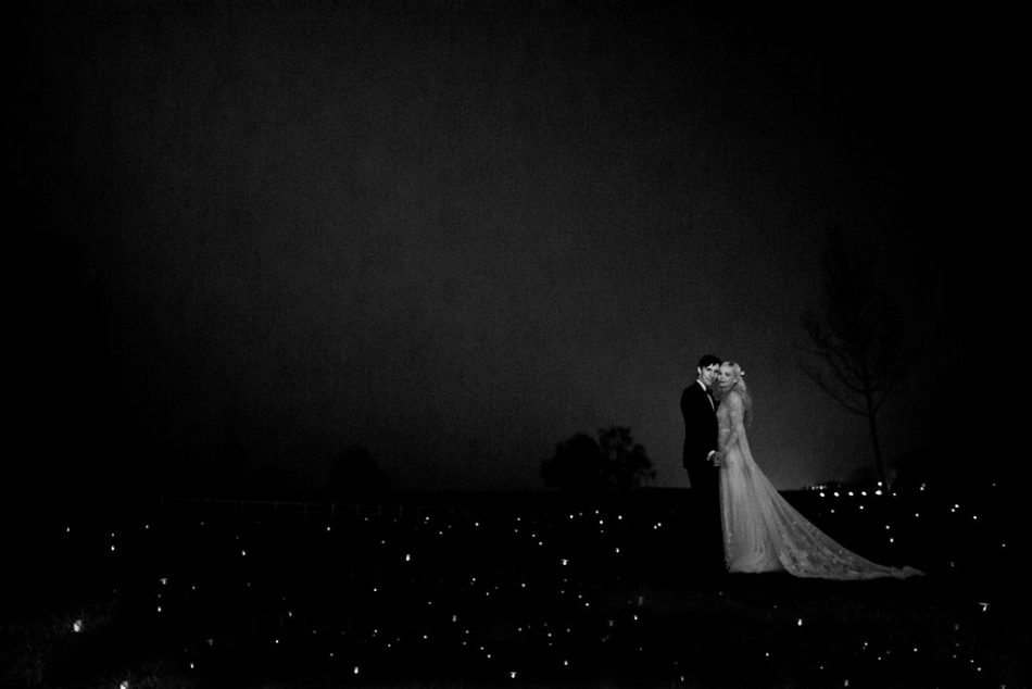 Image of a bride and groom in a field surrounded by tea lights