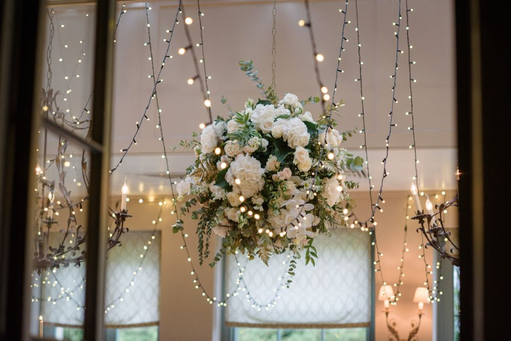Image of a big ball of flowers with fairy lights in a dining room.