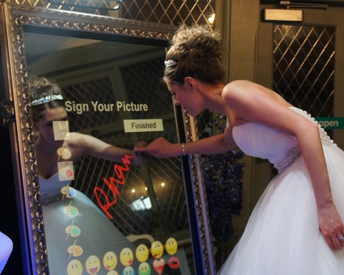 image of a bride wiriting ona magic mirror photobooth.